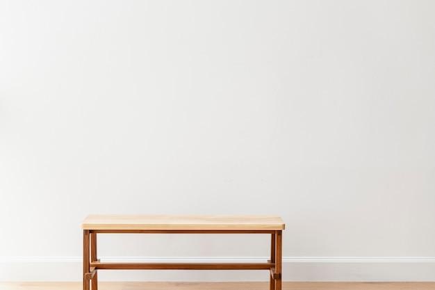 Деревянная скамейка у белой стены