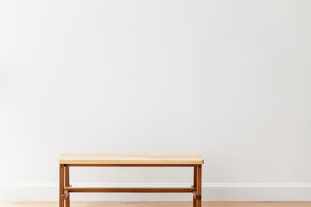 Wooden bench by a white wall