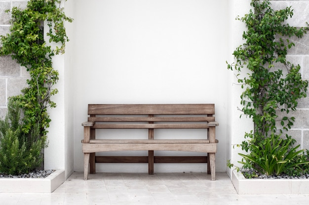 Wooden bench in front of concrete wall with ivy