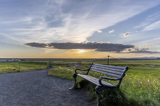 Деревянная скамейка в поле, покрытом зеленью под солнечным светом в исландии