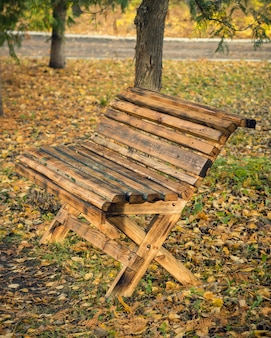 Wooden bench made at home in the autumn park.