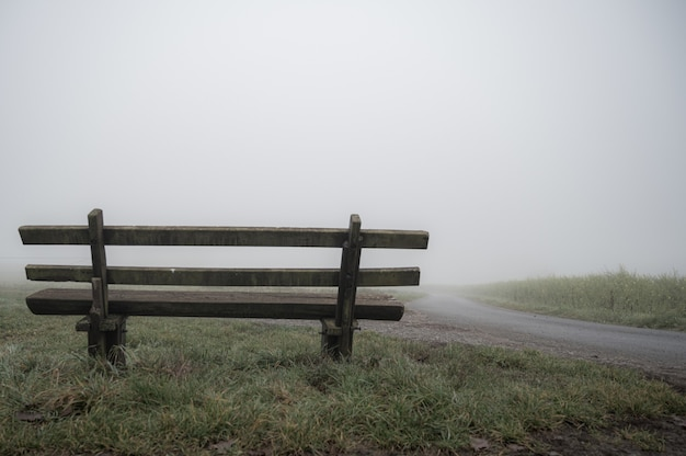 Wooden bench near the road covered with fog - solitude concept