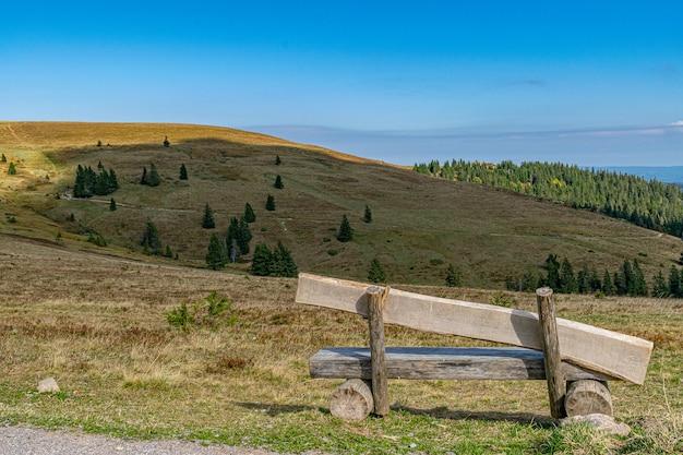 澄んだ青い空の下でのトレッキングやハイキングに最適な丘の上の木製ベンチ