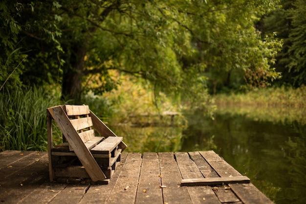 Деревянная скамейка на террасе на берегу озера в окружении зелени