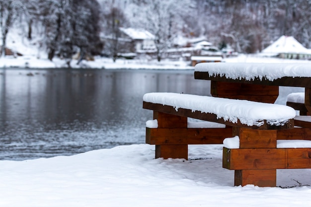 Wooden bench and a table near the lake surrounded by trees covered in the snow during the winter