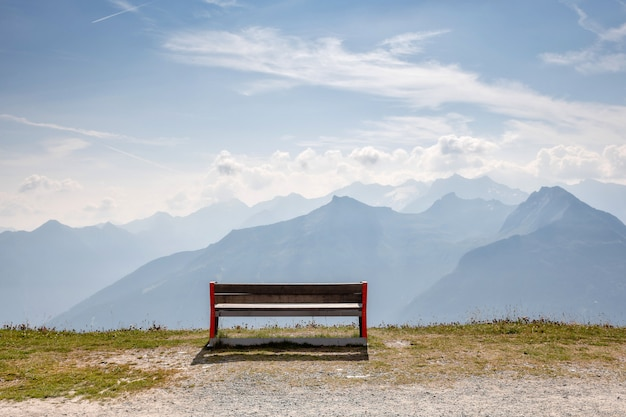 A wooden bench at the top of the alps, a place for tourists to relax and look at beautiful landscapes.