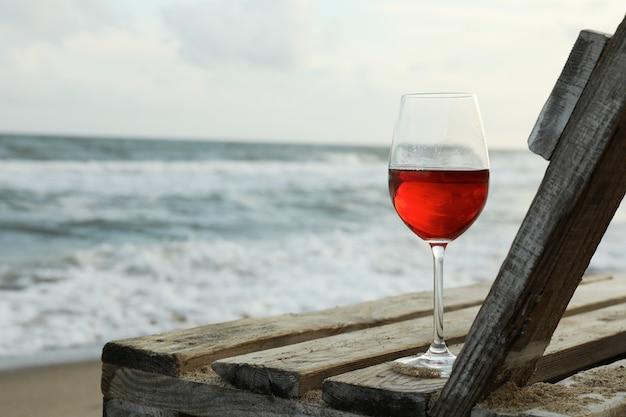 砂浜のビーチでワインのガラスと木製のベンチ