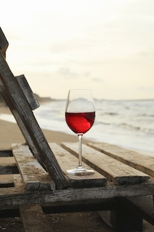 Wooden bench with glass of wine on sandy sea beach