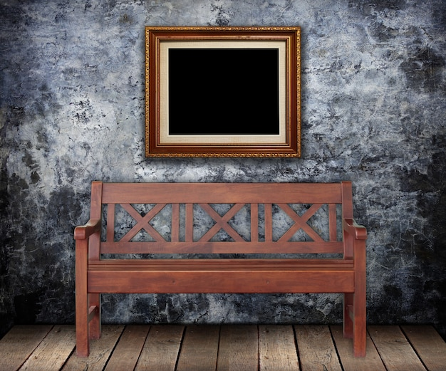 Wooden bench with gold frames on grungy wall.