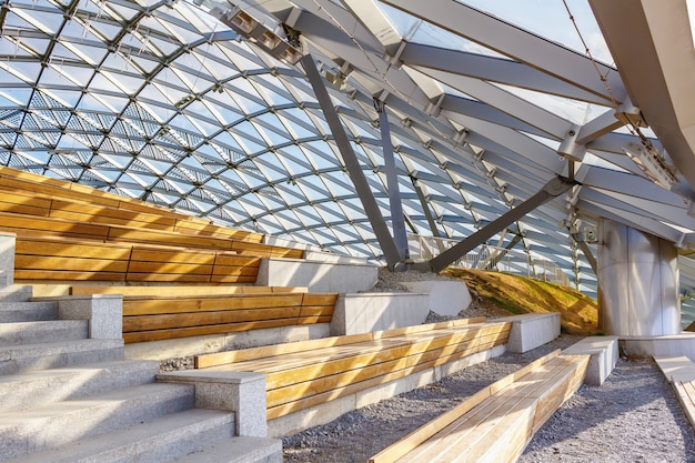 日光の下でガラス屋根の下の木製ベンチ