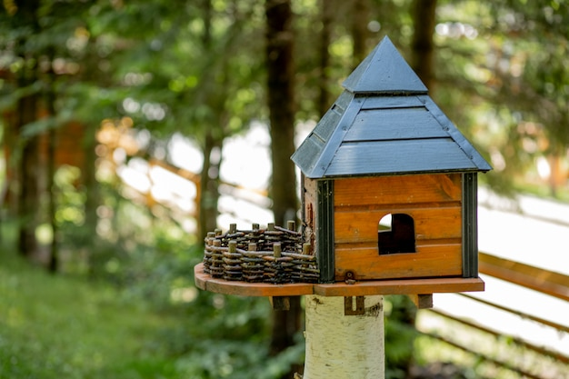 Wooden bird feeder in the form of a house with a roof, attached to a wooden post in a forest among trees in the nature