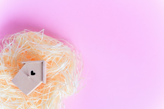 Wooden bird feeder and  in a straw nest on a pink background, top view free copy space. flat lay. easter concept.