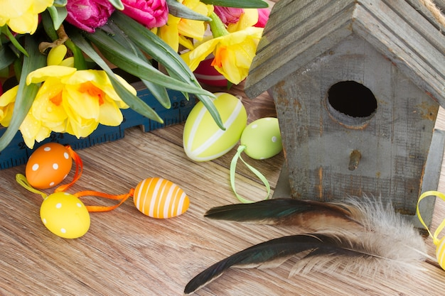 Wooden birdcage with spring tulips and daffodils  and easter eggs
