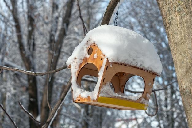 Деревянный скворечник в зимнем лесу. крупный план пустой кормушки для птиц покрыты снегом.