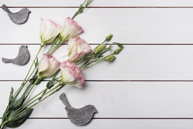 Wooden birds with bunch of eustoma flowers on white textured background