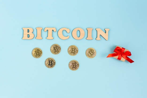 Wooden bitcoin word, golden bitcoins and little gift box on blue surface