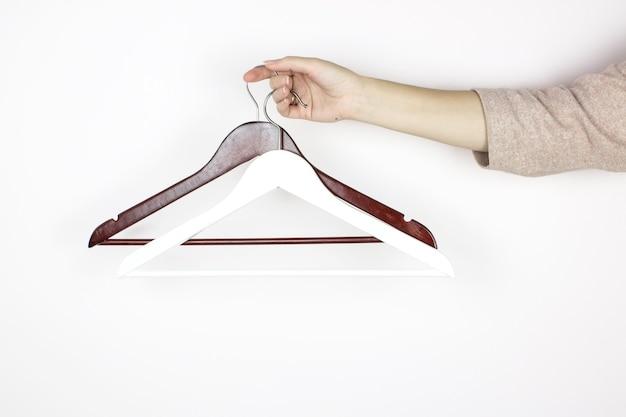 손에 나무 흑백 옷걸이입니다. 상점 개념, 판매, 디자인, 빈 옷걸이.