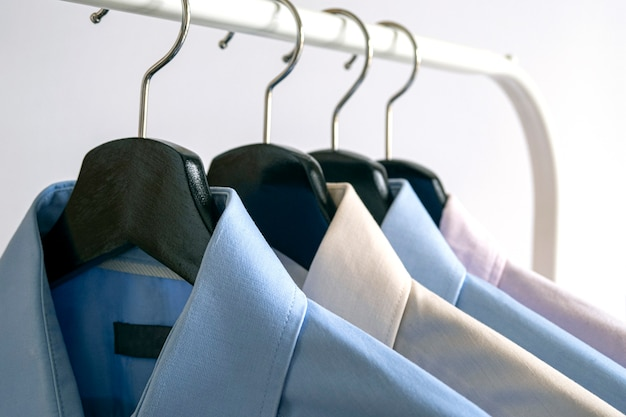 Wooden black hangers with business shirt row of colored shirts on a rack