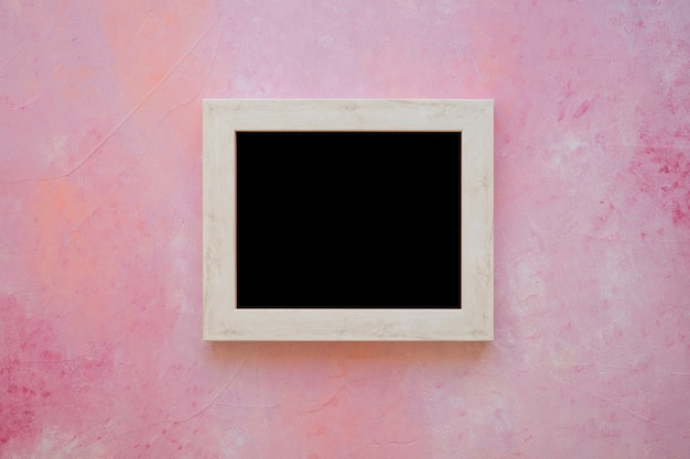 Wooden blackboard on pink painted background