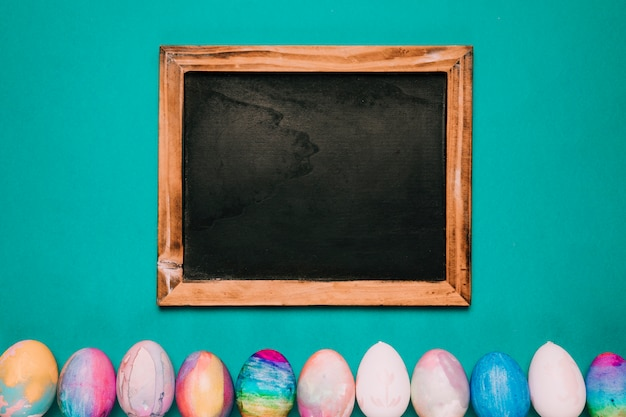 Wooden blackboard over the row of painted easter eggs on green backdrop
