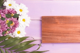 Wooden blank frame with flower decoration on wooden table