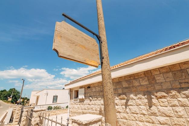Деревянная пустая вывеска на столбе на поверхности кирпичных домов
