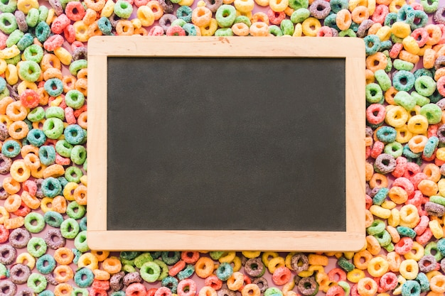 Wooden blank slate over the colorful cereal loop rings background