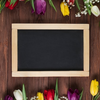 Wooden blank slate with colorful tulips arranged on the top and bottom border over the wooden background