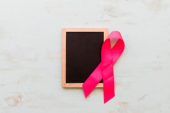 Wooden blank slate with pink awareness ribbon on an old background