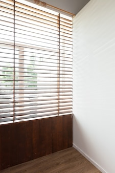 Wooden blinds with sun light in a house room