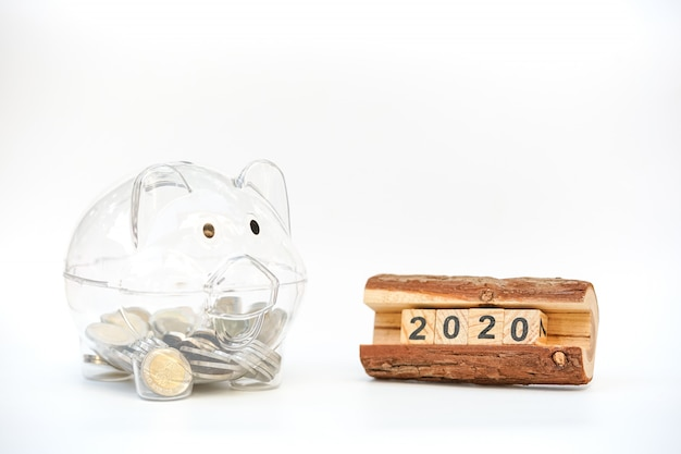 Wooden block 2020 text and piggy bank filled with coins