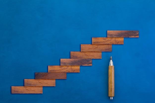 블루 가죽 배경에 나무 연필로 계단으로 나무 블록