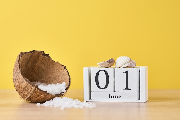 Wooden block calendar with date june 1 and coconut with sea salt on yellow