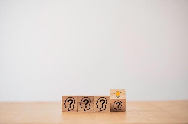 木製のブロックキューブは、人間の質問から賢い思考と解決策の問題へと変化します。それは創造的思考のアイデアとイノベーションのコンセプトです。