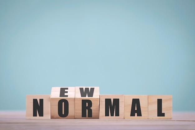 新しい通常の単語のために反転する木製のブロックキューブ。コロナウイルスパンデミック後