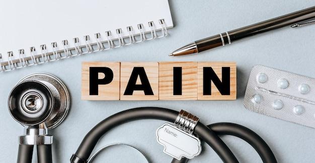 木製のブロックは、聴診器、錠剤、メモ帳、医師のデスクトップ上のペンで痛みという言葉を形成します。