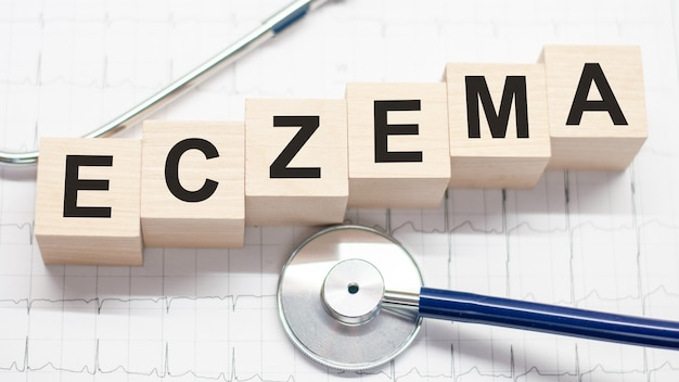 Wooden block form the word eczema with stethoscope on the doctor's desktop