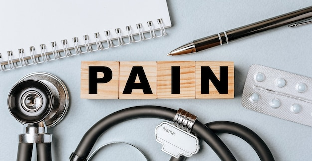 Wooden block form the word pain with stethoscope, pills, notepad, pen on the doctor's desktop.