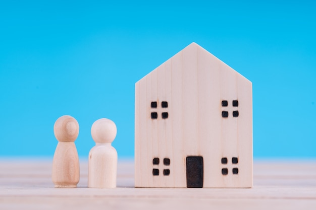 木のブロックの家と人。家族の概念を始める