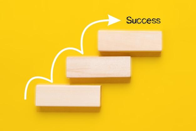 黄色の背景に白い矢印が付いた階段として積み重ねられた木製のブロック。成功へのステップコンセプト
