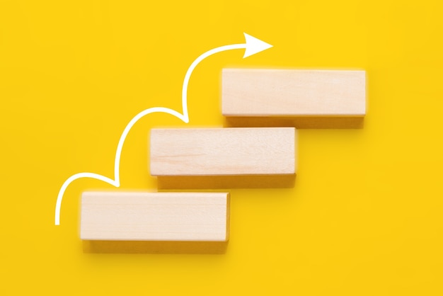 Wooden block stacking as stair with white arrow up on yellow background. ladder of success in business growth concept