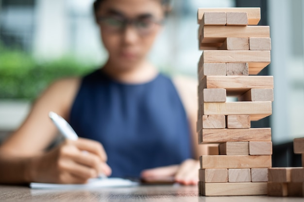 Wooden block tower with businesswoman background
