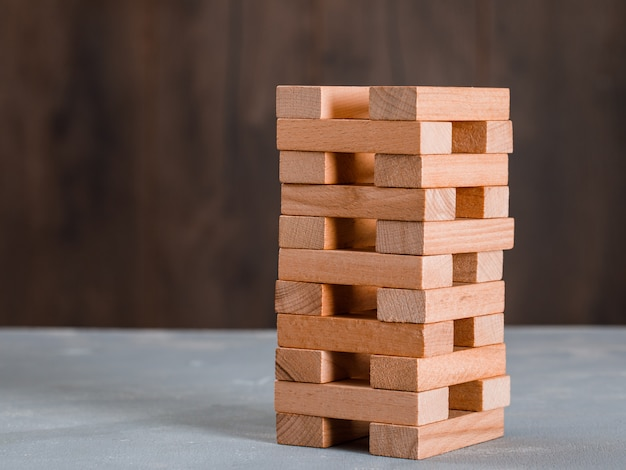 Wooden block tower on wooden and plaster table