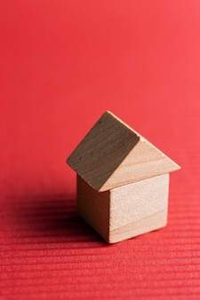 Wooden block toy house on a red surface. conceptual image of acquisition of housing. copy space.