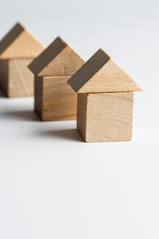 Wooden block toy house on a white surface. conceptual image of acquisition of housing. copy space.