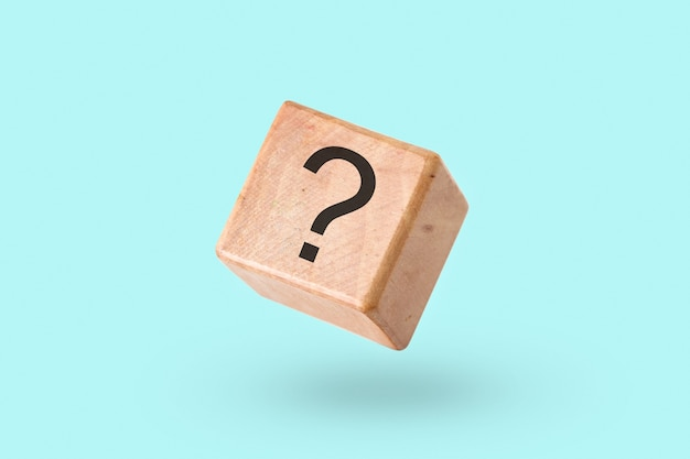 Wooden block on a turquoise with a question mark