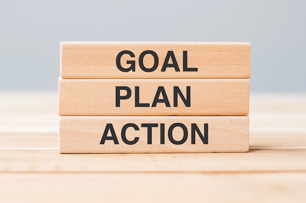 Wooden block with goal, plan and action on table background