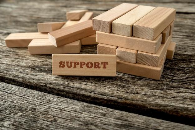 Деревянный блок с опорным словом опирается на конструкцию из множества других блоков. концептуальная техническая поддержка, обслуживание клиентов и помощь.