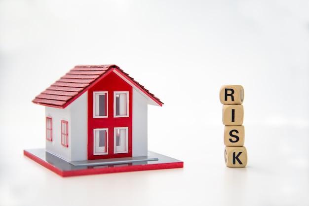 白地に「リスク」と書かれた木造のブロックとモデルハウス。コンセプトリスク管理