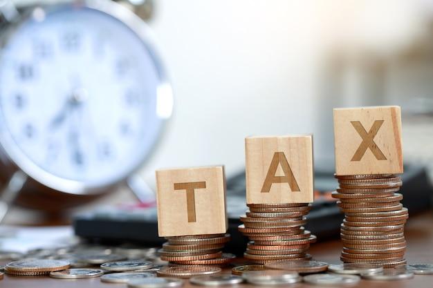 돈에 대한 세금이라는 단어가 있는 나무 블록 테이블에 동전 계산기 더미를 등반
